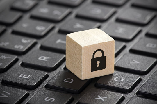 Wooden block with lock graphic on laptop keyboard. Computer security concept.