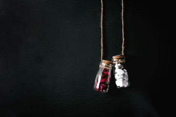 Two bottles full of white and red decorative hearts over black background. St Valentine concept. Copy space