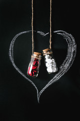 Two bottles full of white and red decorative hearts inside drawn by chalk heart shape over black background. St Valentine concept. Copy space