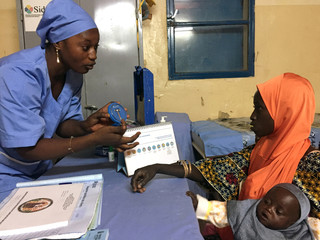 A Marie Stopes nurse explains to mother-of-three Kadidja Toudjani how a contraceptive implant works in Niger's village of Libore, about 20km southeast of the capital Niamey