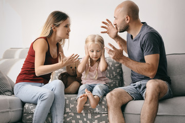 Little girl between arguing parents at home