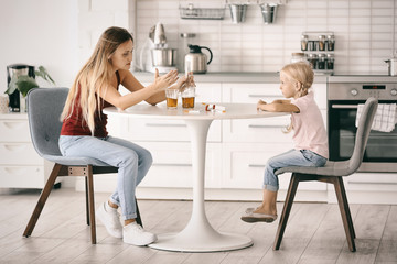 Woman drinking alcohol and scolding little girl in kitchen