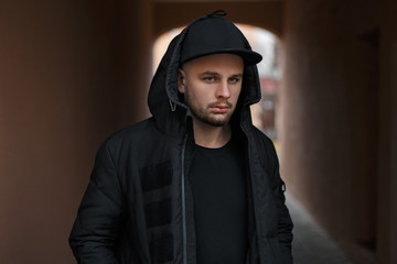 Stylish portrait of a young handsome man in a fashionable black baseball cap in a warm black hood with a hood on the street