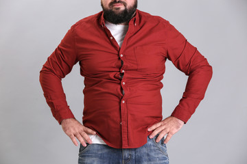 Overweight young man in tight red shirt on light background