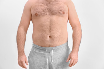 Overweight young man on light background