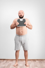 Overweight man holding scales against light wall background