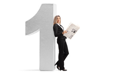 Elegant woman with a newspaper leaning against a cardboard number one