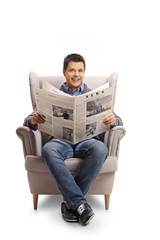 Young man with a newspaper sitting in an armchair