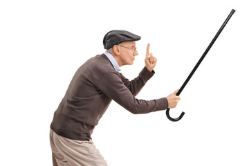 Angry senior holding his cane as a sword and gesturing with his finger