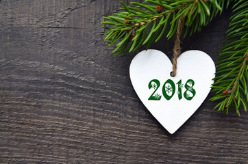 Decorative white wooden Christmas heart with 2018 numbers and fir tree on old wooden background with copy space.Happy New Year 2018 concept.Selective focus.