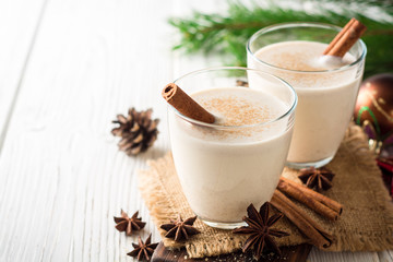 Homemade eggnog with grated nutmeg and cinnamon on white wooden table. Traditional Christmas drink.