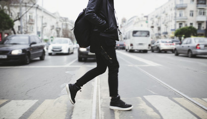 Modern young bearded man in black style clothes is walking at street.