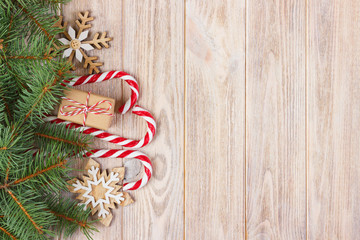 Christmas gift box, candy cane with snowflake and fir tree branch on wooden table