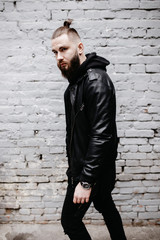 Modern young bearded man in black style clothes posing against brick wall.