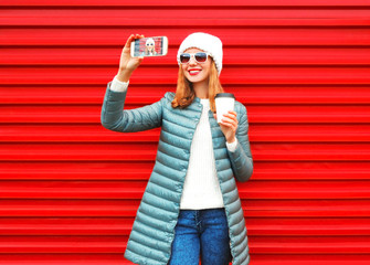 Fashion smiling woman takes a picture self portrait on a smartphone on red background