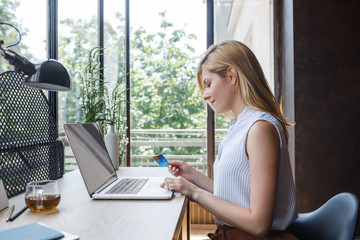 Pretty blonde Caucasian woman typing on laptop and holding credit card.