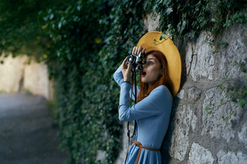 Beautiful young woman in a blue dress walking along the boulevard in the city with a camera