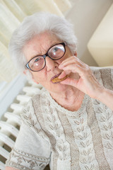 Portrait of senior woman eating cookies.