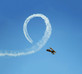 Vintage biplane does loop stunt with smoke trails