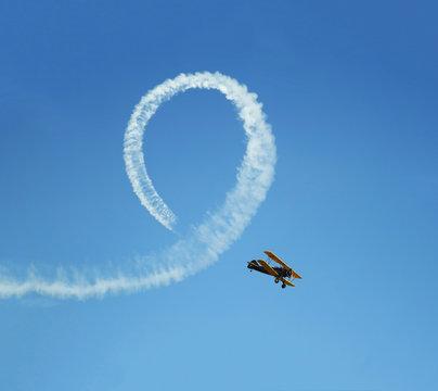 Vintage biplane does loop stunt with smoke trails