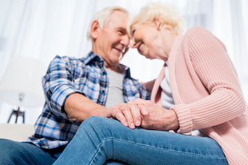 selective focus of happy senior couple looking at each other and holding hands