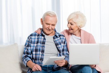 portrait of smiling senior wife and husband using digital devices at home