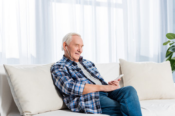 side view of smiling senior man in earphones with smartphone resting on sofa at home