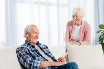 selective focus of senior man in earphones listening music while wife standing near by at home