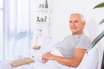 side view of senior man with book resting in bed and looking at camera at home