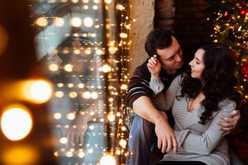 Couple of lovers hugs sitting on the windowsill in the Christmas loft studio. guy is hugging the girl.
