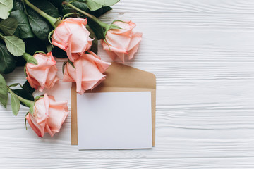 Blank paper note with envelope and pink rose on wooden background