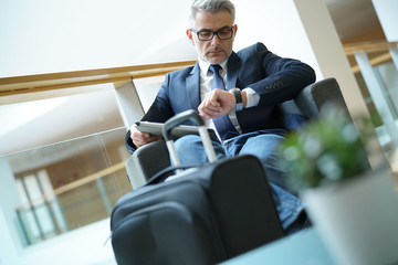Businessman in airport lounge checking time on watch
