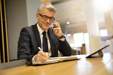 Businessman in restaurant talking on phone