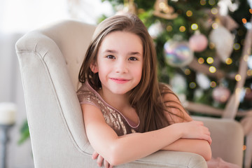 Portrait of a cute beautiful girl on a background decorated Christmas tree