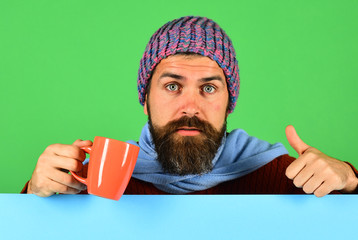 Hipster with beard and serious face shows thumbs up