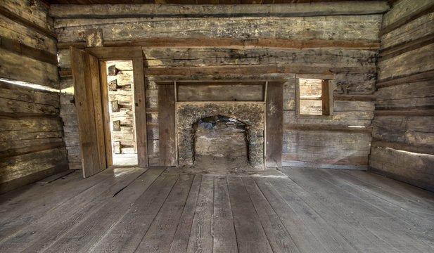 Pioneer Log Cabin Interior. Wooden interior of historic pioneer cabin living room with hardwood floor and fireplace.