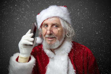 Santa Claus using smartphone - calling phone or texting a message