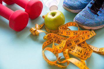 Diet slimming weight with green apple and measuring tap, scale weight on the wood plate, vegetables, dumbbells, colourful background.  Diet and Healthy Concept