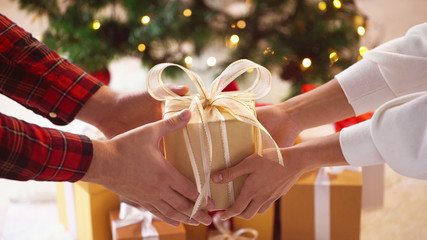 close up of couple hands with christmas gift box