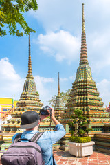 Tourist man take a picture of stupa with a camera in famous temple of wat pho, bangkok, thailand