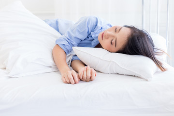 beautyful asian woman in blue shirt sleep on white bed with window light