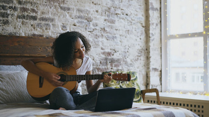 Curly african american teenager girl concentraing learning to play guitar using laptop computer...