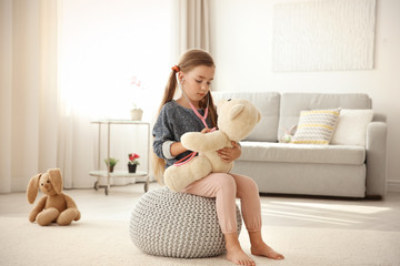 Adorable little girl examining teddy bear with stethoscope at home