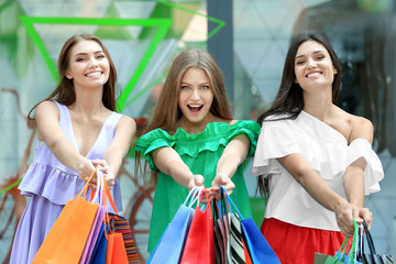 Young women with shopping bags on city street