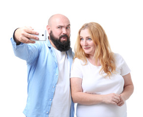 Overweight couple taking selfie on white background