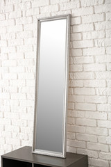 Modern mirror on stand near brick wall