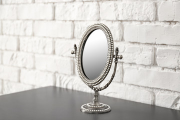 Vintage small mirror on table near brick wall