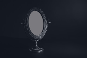 Vintage small mirror on black background