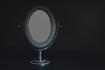 Vintage small mirror on black background