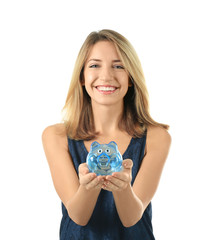 Beautiful young woman with piggy bank on white background